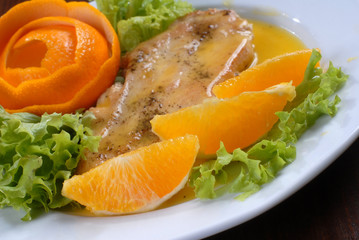 a plate of delicious juicy pork chop served with orange
