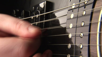 Closeup of a hand with a pick playing a guitar