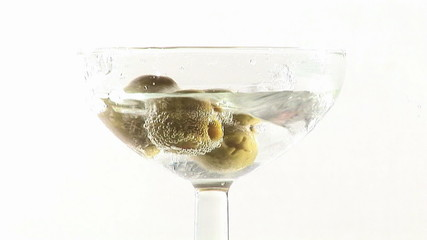 Martini cocktail with olives falling down footage