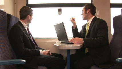 Footage of two businessmen talking in a train