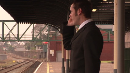 Footage of a businessman on phone in a train station