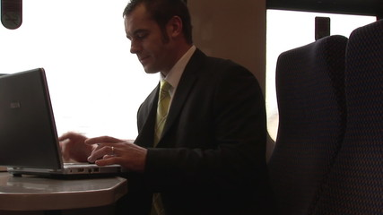 Busy businessman working with a laptop in a train
