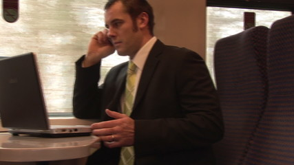 Businessman on a mobile and working with a laptop in a train