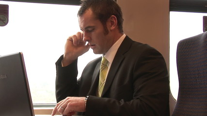 Businessman on phone and using a laptop in a train
