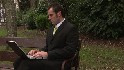 Young businessman using a laptop in a park