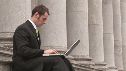 Footage of a business man Outdoors Using Laptop