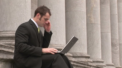 Footage of a Business man Outdoors Using Laptop and phone