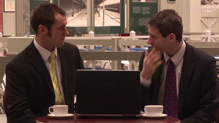 Two businessmen talking in a bar with a laptop