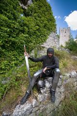 Ritter mit Schwert und Beinschienen sitzt vor alter Burg