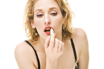 blond woman putting red lipstick on lips during makeup