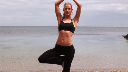 Attractive woman doing yoga on the beach