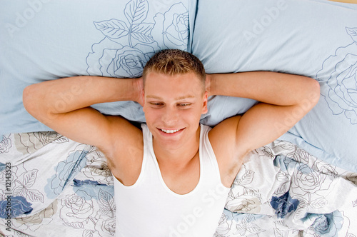 tired young male relaxing on his bed