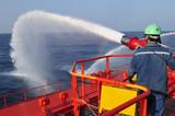 Fireman testing a foam/water gun poster