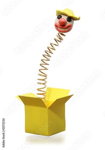 Leinwandbild Motiv Metal spring with clown head jumping from yellow box