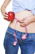 Woman measuring her small waist and holding red apple