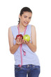 young woman holding two apples and measuring tape