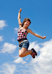 Cute happy girl jumping under a blue sky