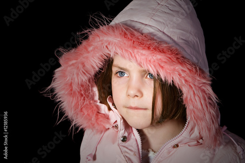 Cute Child in Pink Hooded Top against Black Background
