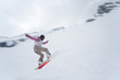 Girl with snowboard jumping of a hill