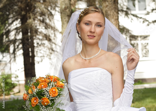 Beautiful bride with bouquet in sunny day