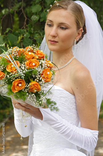 Beautiful bride looking on bouquet in sunny day