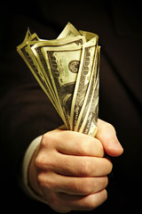 man's hand holds dollars