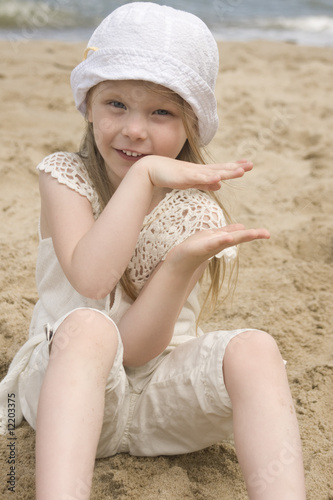 The girl holds hands sitting on the beach