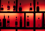 Fototapeta Back lit bottles in a cocktail bar