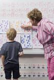 Teacher Explaining Calendar to Little Boy