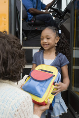 Mother Handing Daughter Backpack on School Bus