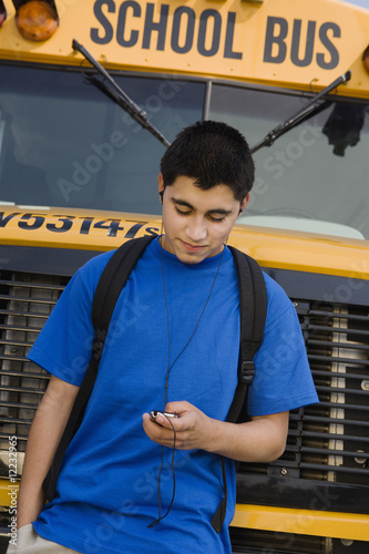 Teenager Boy Listening to MP3 Player by School Bus