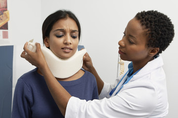 Female doctor puting brace on patient's neck