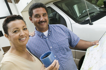 Mid-adult couple standing beside caravan and looking at camera