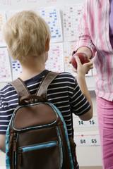 Little Boy Handing Teacher an Apple
