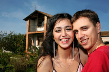 Young happy couple beside their new house
