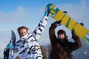 two happy young women with snowboards