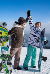 two happy snowboarders giving each other a high five