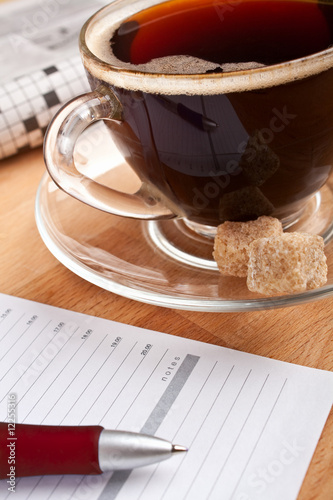 breakfast with coffee, newspaper and a notepad