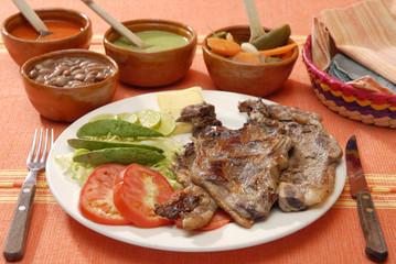 Costilla de res asada con ensalada y frijoles. México