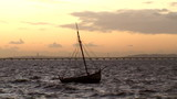 Fishing boat in rough sea at sunset
