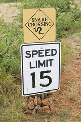 Snake crossing and speed limit signs.