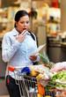 Frau kontrolliert Kassenzettel im Supermarkt