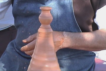 Potters hands creating a clay vase on the turning wheel