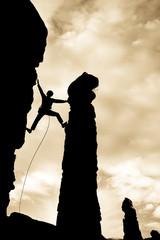 Rock climber reaching across a gap.