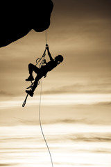 Rock climber dangling from a rope.
