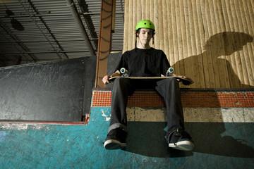 Skateboarder sitting on ramp