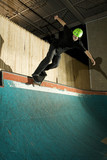 Skateboarder doing backside smith grind on ramp poster