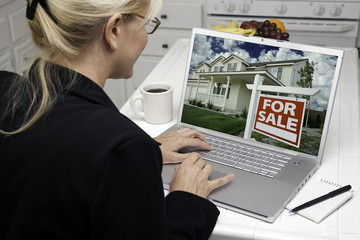 Woman In Kitchen Using Laptop for Real Estate