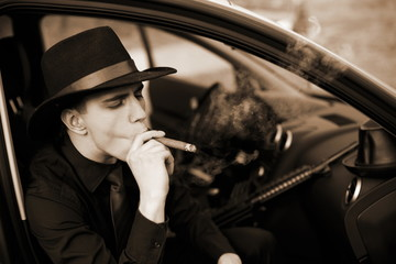man in car with cigar and rifle