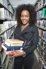 Female University student holding books in library, portrait